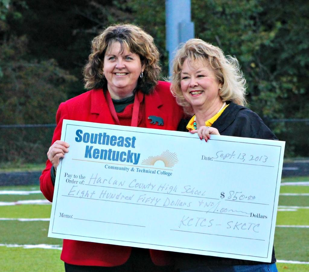 Southeast Kentucky Community and Technical College President Dr. Lynn Moore (right) presented a check to Harlan County HIgh School Principal Edna Burkhart before the Knox Central-Harlan County football game at Coal Miners Memorial Stadium.