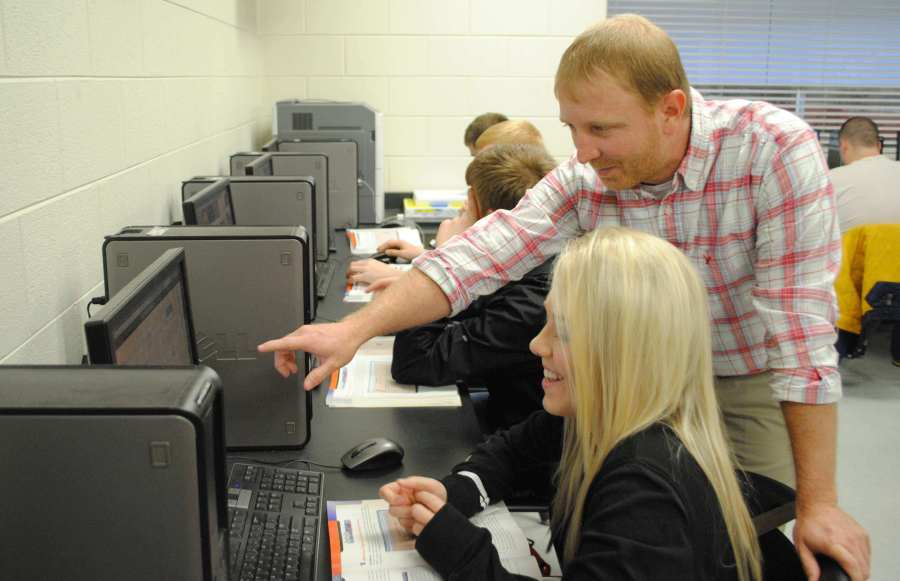 Harlan County High School web design instructor Scott Pace worked with Abby Landis on a project during a class. The HCHS program allows students to create web pages for area businesses and organizations.