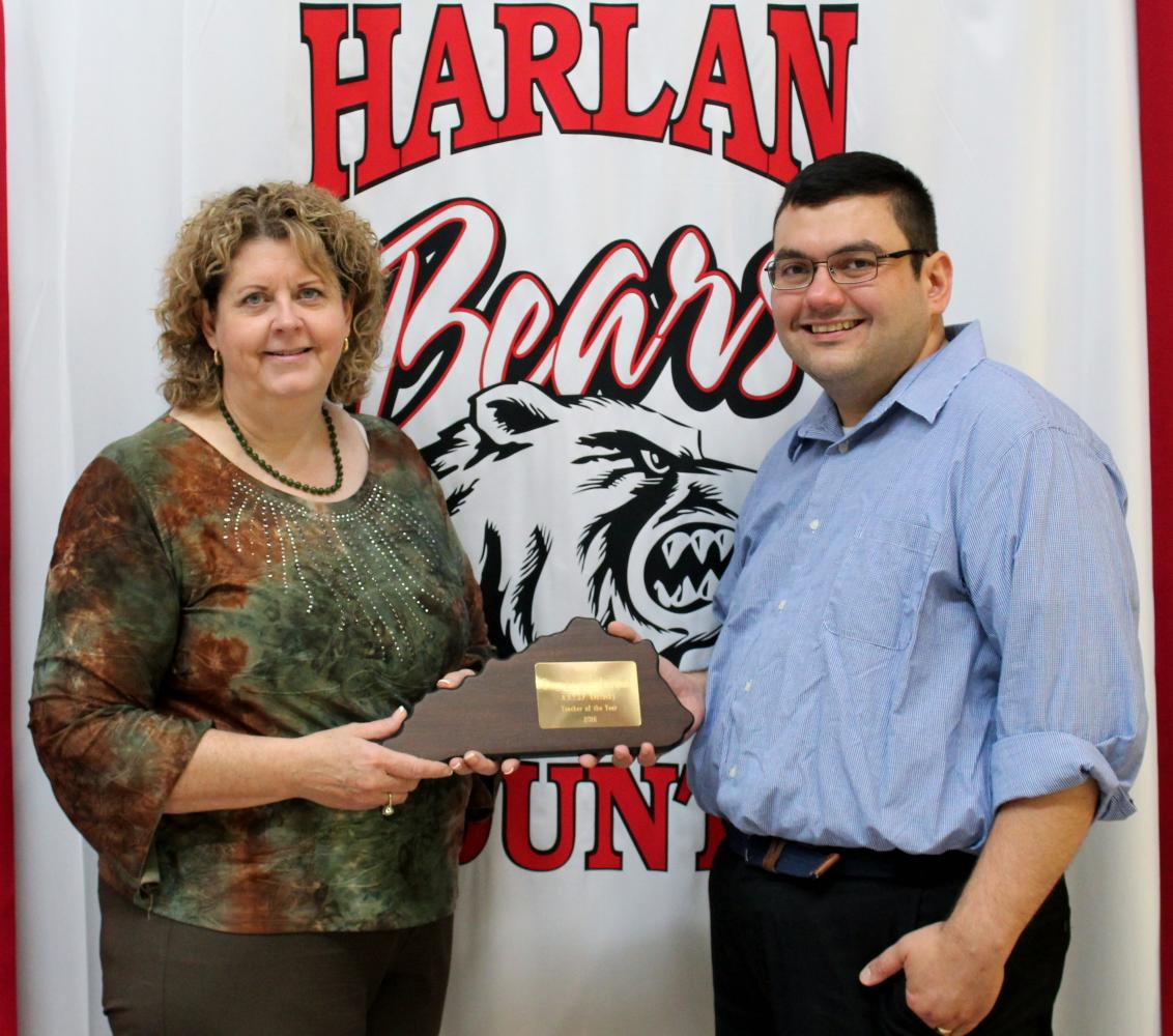 Harlan High School Principal Edna Burkhart presented an award to Spanish teacher Emmanuel Anama-Green for his recent selection as president-elect of the Kentucky World Language Association.