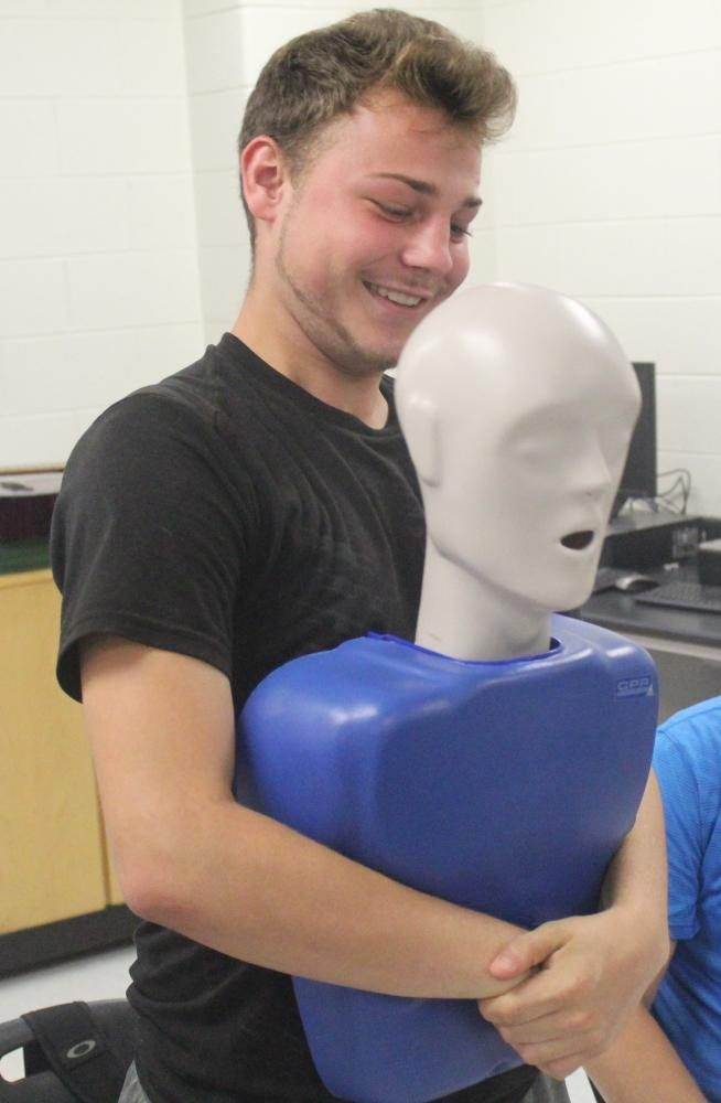 HCHS senior Justin McQueen practiced the Heimlich maneuver as part of the lesson on saving lives by health coordinator Christy Whitaker in John Henson's life skills classes.