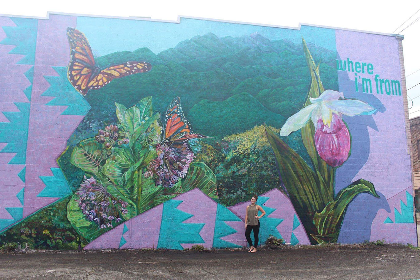 Former Harlan County High School student Emily Eldridge stood in front of the mural recently completed in Cumberland on the side of Buff's Bows and Gifts. Volunteers spent several days and used quite a bit of paint to complete the project.